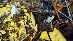 En man inspekterar ruinerna efter sitt kollapsade hus.
