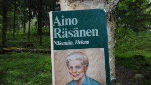 Aino Räsäsen kirja Näkemiin, Helena nojaa koivun kylkeä vasten.