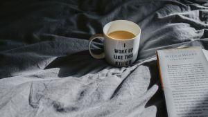 Kaffe och bok i en säng.