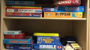 Spel och pussel i en bokhylla.