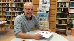 Modersmålsläraren Kenneth Nygrén står vid ett bord i skolans bibliotek.