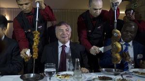 Brasiliens president Michel Temer med servitörer som skär kött från stora spett på vardera sidan om sig.