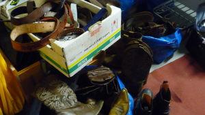 Läderstövlar/boots i en hög. I en papplåda finns olika läderbälten. Accessoarer till teaterkläder.
