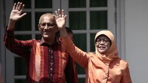 Singapores nyvalda president hälsar på folket tillsammans med sin man.