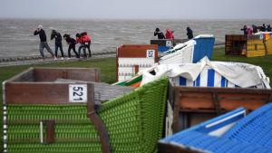 Barn kämpar sig fram mot vinden på stranden i Norddeich.