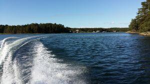 Vågor efter en motorbåt sköljer stränder i skärgården. I bakgrunden syns båthus.