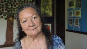 Porträtt av poeten Elsa Lopez som ler i kameran med pärlhalsband runt nacken