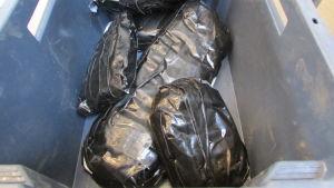 Flera svarta paket som innehåller knark i en blå plastlåda.