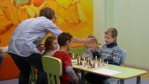 En schacklärare berömmer barn, fyra barn sitter vid ett bord.