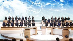 """Värdsledare står uppradade framför stor vägg där det står """"one Planet Summit""""."""