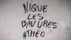En graffiti på väggen till en Parisskola svär över polisens våld.