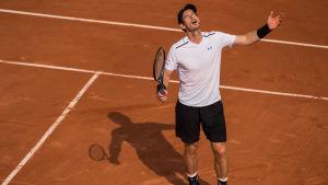 Tennisstjärnan Andy Murray håller upp händerna i luften.