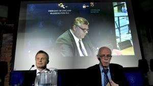Juha Savolainen och Thomas Elfgren under ett presstillfälle. Timo Soini är live på en skärm i bakgrunden.