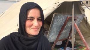 En kvinnlig afghansk lärare i svart huvudduk utanför en tältskola