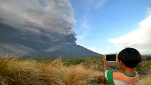 En pojke fotograferar rökmolnet från vulkanen Agung i Kubu, Bali, den 26 november.