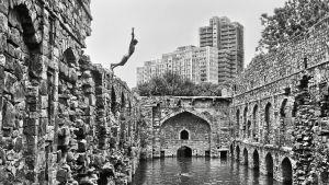 Mies hyppää uimaan rapistuvan kivimuurin päältä. Raghu Rain valokuva