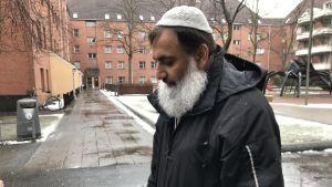 En man med huvudbonad och stort grått skägg på en innergård.