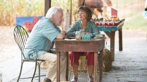 John och Ella vid ett cafébord utomhus.