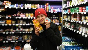 patrik Kumpulainen håller matprodukter som är på rabatt.