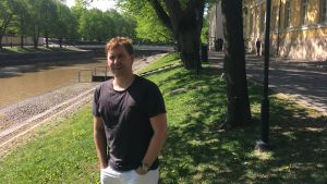 Jonas Lagerström står vid åstranden i Åbo en solig sommardag.