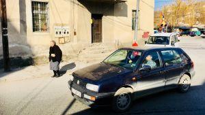 En liten och gammal, smutsig bil kör förbi en äldre dam i den makedonska staden Veles.
