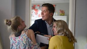 Donna (Alina Tomnikov), Mira (Essi Hellén) ja André (Eero Ritala) tappelevat kahvikoneesta Donnan olohuoneessa.