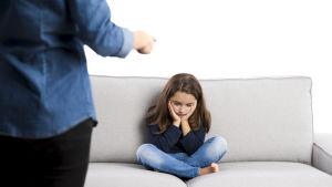 En flicka på en soffa blir åthutad av en förälder.