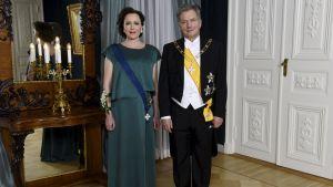 Jenni Haukio och Sauli Niinistö poserar inför slottsbalen.