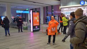 Orangeklädd personal delar ut metrokassar till passagerare i Mattby bussterminal.