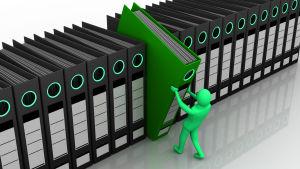 En grön människofigur drar ut en grön mapp ur en lång rad med svarta mappar.