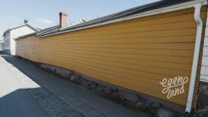 En lång, gulmålad husvägg i Brahestad.