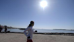 Joggande flicka vid en strand.