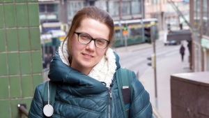 Maria Eliseeva iklädd mörkgrön täckjacka står och tittar rakt in i kameran med några stora våningshus i bakgrunden.