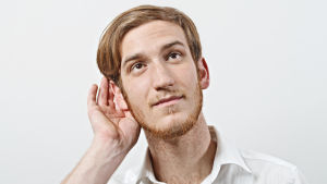 En man håller sig bakom ena örat och lyssnar uppmärksamt.