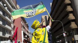 En sydafrikansk demonstrant viftar med en fackföreningsflagga.