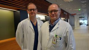 Två manliga läkare, en ung och en i övre medelåldern, står i en sjukhuskorridor med vita läkarrockar på sig.