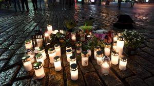 I förgrunden gravljus och blommor, i bakgrunden står människor och iakttar. Ljusen är på den plats där knivhuggningen i Åbo ägde rum fredagen den 19.8.