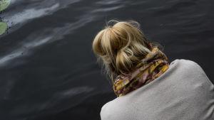 Nainen järven rannalla.