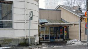 En ingång till en affärslokal. Till vänster syns ett äldre hus i sten.