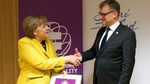 Juha Sipilä överräcker priset åt Angela Merkel.