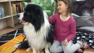 Flicka och hund sitter på golvet.