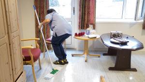 Hemvårdare städar lägenhet.