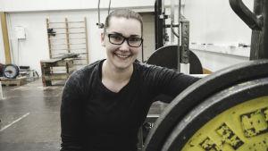 En kvinna sitter bredvid en skivstång med en vikt på. Hon ler.