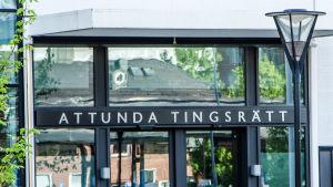 Tegelhus speglar sig i glasdörrarna vid huvudentrén till Attunda tinsrätt.
