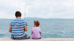 En pappa sitter med sin son på en brygga med ett fiskespö. I bakgrunden syns hav och en molnig himmel.