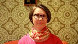 Kvinna i brun page och glasögon mot en vägg med mönstrad, grön tapet i 70-talsstil. Fotad på Helsingfors stadsmuseum.