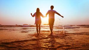 Man och kvinna håller varandra i handen på en strand i solnedgången.