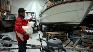 hamnkapten Göran Berghem med hunden Nappi i famnen betraktar en av båtarna i båtförvaringshallen vid Baggö Marina.
