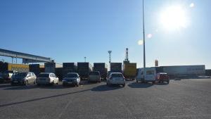 En bild på nio långtradare som står uppradade på en parkering. Bilden är tagen motljus och himlen är blå.