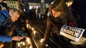 Personer tänder ljus till minnet av offren i Charlie Hebdo-massakern